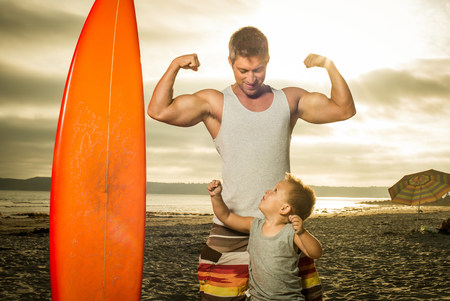 3 4 years: Young man and son flexing muscles on beach