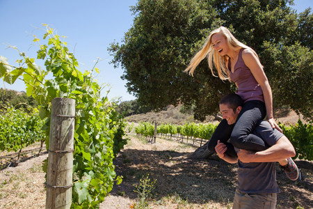 Young couple in vineyard,man giving woman piggy back LANG_EVOIMAGES