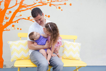 Father sitting on bench with two daughters on lap