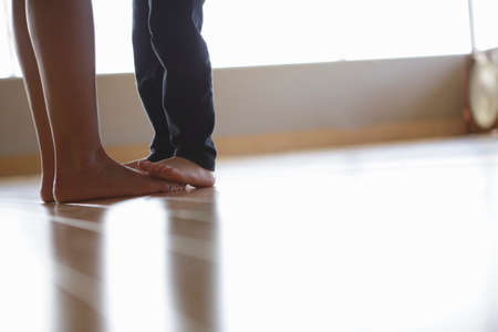 keep in touch: Legs of mother and daughter in exercise studio