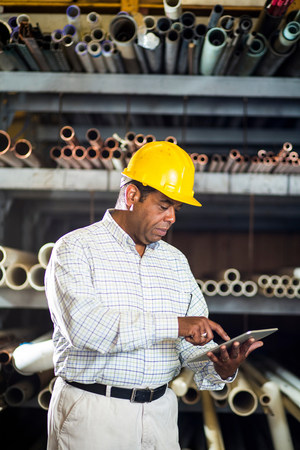 american field service: Man in warehouse with digital tablet LANG_EVOIMAGES