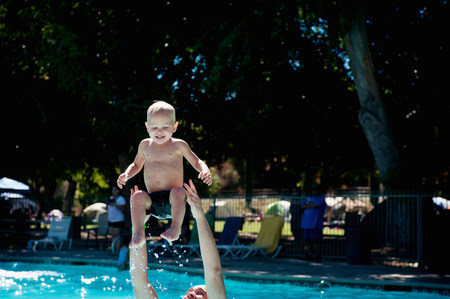 extreme close up: Young male toddler in swimming pool with father