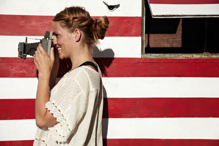 stripy: Woman taking photograph using vintage camera