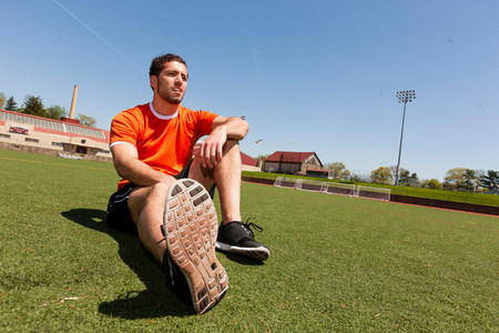 species living: Young man taking a break on sport stadium grass LANG_EVOIMAGES
