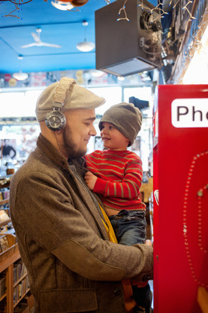 payphone: Father holding young son by public telephone