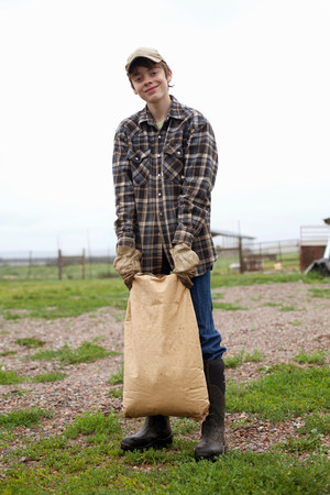 Boy carrying sack of feed