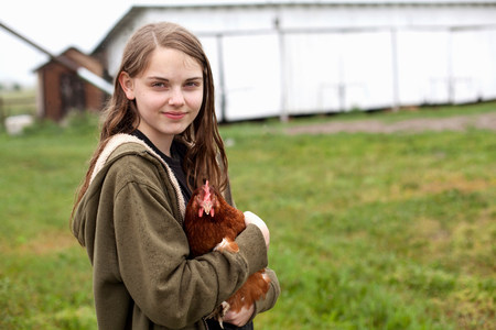Girl carrying hen