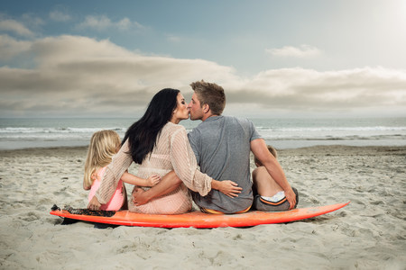 Young family sitting on surfboard on beach with parents kissing LANG_EVOIMAGES