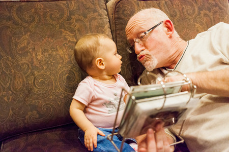 0 1 years: Grandfather and baby granddaughter on sofa