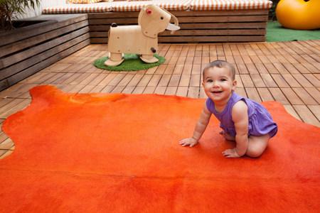 floor covering: Baby girl crawling on orange rug,portrait
