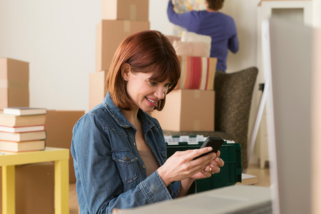 new age: Woman looking at cellphone whilst moving house