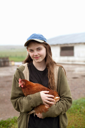 farmyards: Girl carrying hen