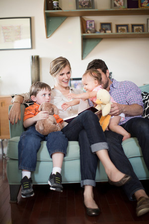 woman hanging toy: Parents with two children sitting on sofa