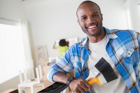 afro caribbean ethnicity: Mid adult man holding paintbrushes