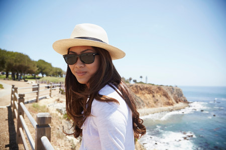fenced in: Portrait of young woman wearing sunhat,Palos Verdes,California,USA LANG_EVOIMAGES