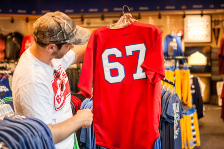 coathangers: Man holding up t-shirt in store