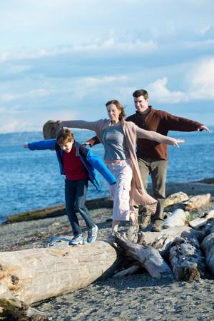 Family walking across tree trunk at coast