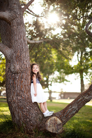 Portrait of girl standing on tree trunk LANG_EVOIMAGES