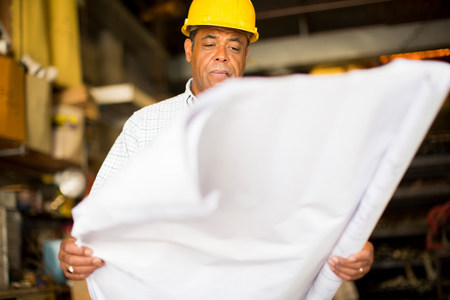 Man in warehouse holding up blueprint