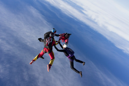 team from behind: Small group of skydivers in formation LANG_EVOIMAGES