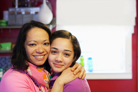 Portrait of mother hugging daughter in kitchen