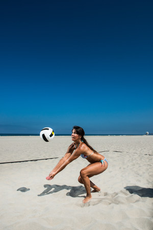 Female beach volleyball player digging ball