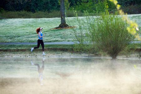 Teenage girl jogging by misty lake LANG_EVOIMAGES