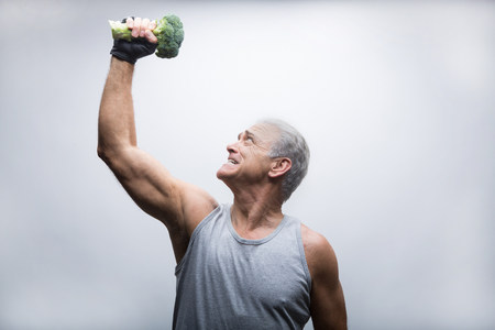 athletic wear: Senior man looking up and lifting broccoli LANG_EVOIMAGES