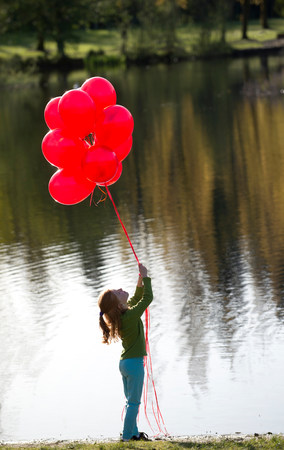 top 7: Young girl in front of lake with bunch of red balloons