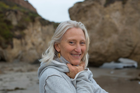 coldness: Mature woman wearing grey sweater on beach,smiling LANG_EVOIMAGES