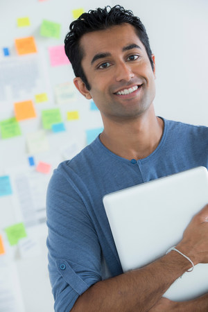reminding: Portrait of male office worker holding digital tablet