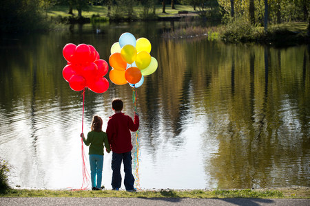 lit image: Brother and sister in front of lake with bunches of balloons