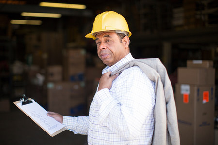 Portrait of man in warehouse with clipboard LANG_EVOIMAGES