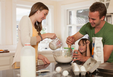 Young girl baking with older brother and sister