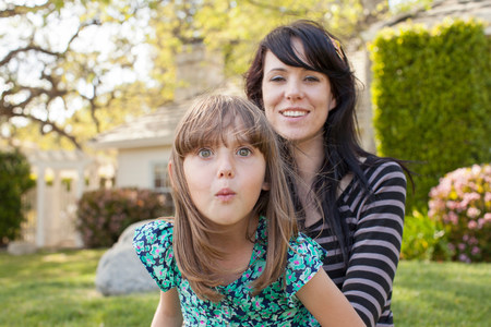 puckered lips: Portrait of mother and daughter pulling face in garden