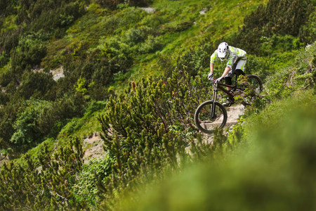 Mountain biker riding down steep hill path LANG_EVOIMAGES