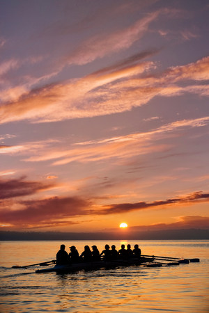Eight people rowing at sunset