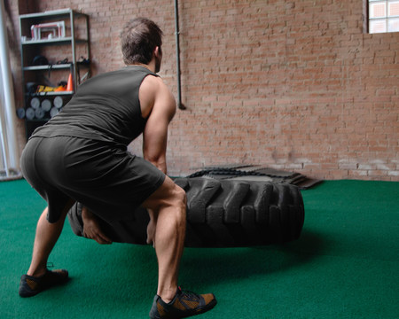 low self esteem: Male bodybuilder lifting tyre