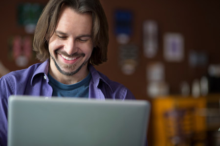 technology: Portrait of young man using at computer in cafe LANG_EVOIMAGES