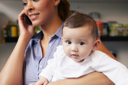 Mother holding baby girl whilst on the phone LANG_EVOIMAGES