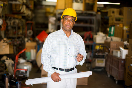Portrait of man in warehouse holding blueprint LANG_EVOIMAGES