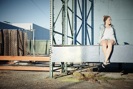 cross legged: Woman sitting on wall in industrial area LANG_EVOIMAGES