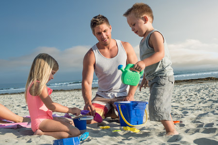 Young man playing with son and daughter on beach