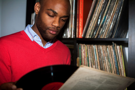 lps: Portrait of young man removing vinyl record from sleeve