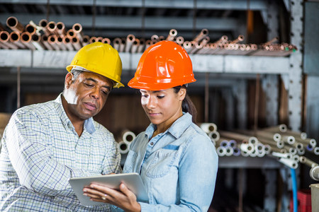 american field service: Man and woman in warehouse looking at digital tablet