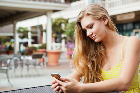 Frau Blick auf Handy LANG_EVOIMAGES