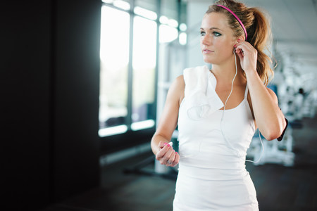 armbands: Young woman using earphones while exercising in gym LANG_EVOIMAGES