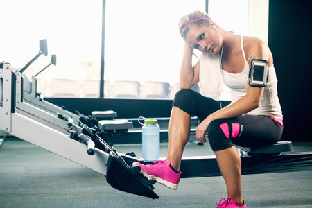 exhausting: Young woman taking a break from exercising in gym