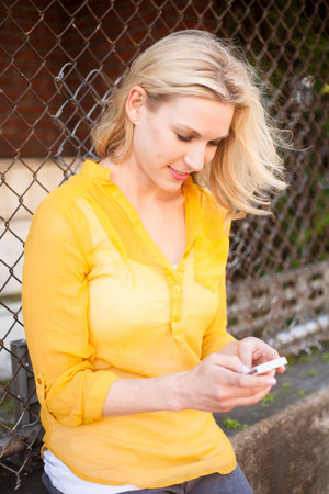 Woman using mobile phone against chain link fence LANG_EVOIMAGES