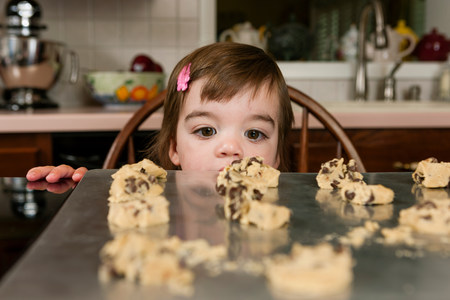 Close up portrait of young female toddler looking at currant cakes LANG_EVOIMAGES